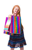 Child shopping. Happy fashion little redhead girl with shopping bags — Stock Photo