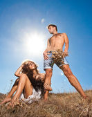 Fashion young couple standing together in a wheat field — Stock Photo