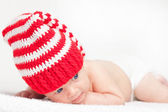 Baby in funny red hat — Stockfoto