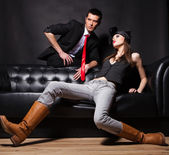 Handsome fashion couple sitting on sofa — Stok fotoğraf