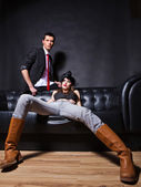 Handsome fashion couple sitting on sofa — Stock Photo
