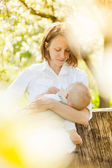 Mother feeding her baby with breast outdoor shot — Stock Photo