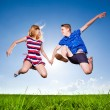 Fun couple in jump on the outdoor background — Stock Photo #42361255