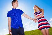 Para trzymając się za ręce i chodzenie w zielone pole — Zdjęcie stockowe
