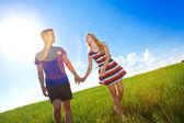 Couple holding hands and walking in green field  — Стоковое фото