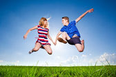 Fun couple in jump on the outdoor background  — Foto de Stock