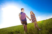 Couple holding hands and walking in green field  — Stock Photo