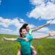 Happy young couple pointing out on summer field — Stock Photo #5548309