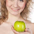 Smiling attractive woman offers a green apple, isolated — Stock Photo