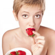 Young blonde with red lipstick. Eating strawberries — Stock Photo #12749599