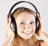 Girl with headphones on the grey background — Stock Photo