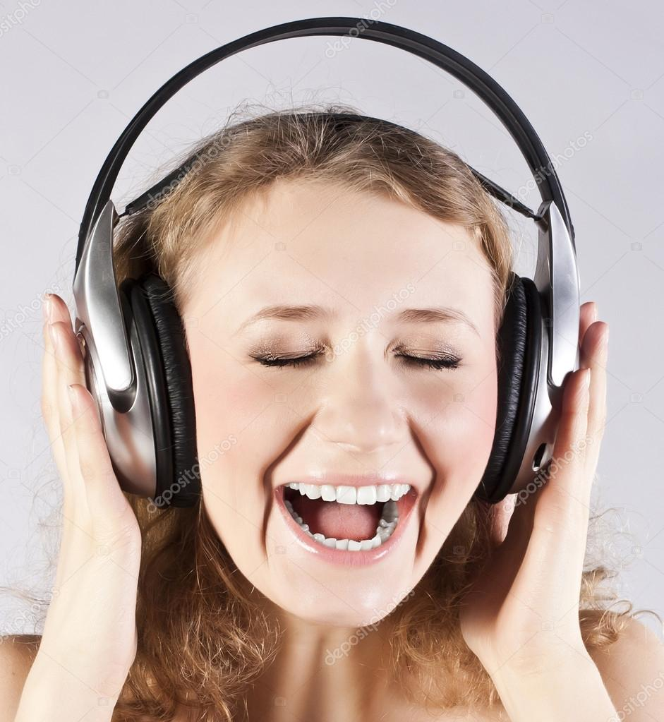 Happy blonde with headphones. Studio gray background — Stock Photo #12749475