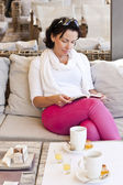 Erwachsene Frau, die Lektüre eines Buches in einem café — Stockfoto