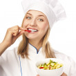 Stock Photo: Young chef taste salad. Studio white