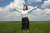 Portrait of happy businesswoman in green field — Stock Photo