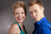 Cheerful young couple standing in studio — Stock Photo