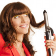 Beautiful woman curling her brunette hair — Stock Photo