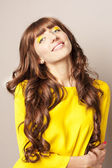 Woman in yellow with luxurious hair — Stock Photo