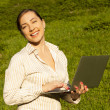 Stock Photo: Young womwith laptop on green grass