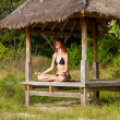 Woman doing yoga meditation in tropical gazebo — Stockfoto