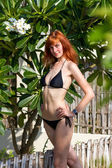Young woman in bikini near tropical bush — Стоковое фото