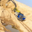 Stock Photo: Excavator Loading Dumper Truck