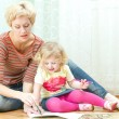 Mother with a little daughter drawing — Stock Photo #24414145