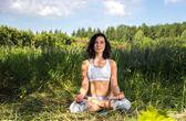 Mujer joven haciendo yoga al aire libre — Foto de Stock