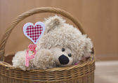 Teddy bear holding heart in basket Valenyine — Stock Photo