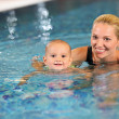 Young cheerful mother and little son in a swimming pool — Stock Photo #12171973
