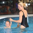 Young cheerful mother and little son in a swimming pool — Stock Photo #12171981