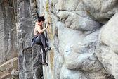 Rock climber struggling to make the next movement — Stock Photo