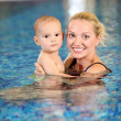 Young cheerful mother and little son in a swimming pool — Stock Photo