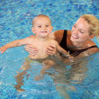 Stock Photo: Young mother and little son having fun in swimming pool