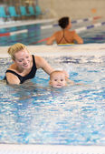 Young mother and little son in a swimming pool — Stock Photo