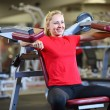 Cheerful young womworking out on exercise machine — Stock fotografie #12449197