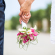 Closeup view of married couple holding hands and carrying bride's bouquet — Stock Photo