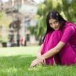 Young girl sitting on the grass in the park — Stock fotografie #12759993