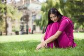 Ung flicka sitter på gräset i parken — Stockfoto