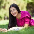 Stock Photo: Young girl lying on grass in park, reading magazine