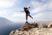 Young man standing on a rock against picturesque view of sea — Stock Photo