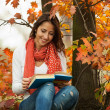 Young girl reading book in autumn park — Stock Photo
