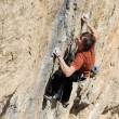 Stock Photo: Rock climber struggling to make next movement