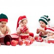 Four babies in xmas costumes playing with gifts — Stock Photo #15634223