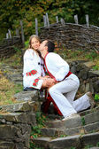 Young romantic couple in Ukrainian style clothes outdoors — Stock Photo