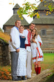 Two young couples in Ukrainian style clothing posing outdoors — Stock Photo
