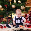 Cute baby boy with Christmas gifts — Stock Photo