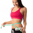 Beautiful young girl checking her waistline with a measuring tape — Stock Photo