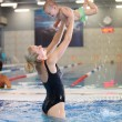 Young mother and little son having fun in a swimming pool, motion blurred image — Stock Photo