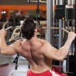 Rear view of young fitness guy working out on exercise machine - Stock Photo